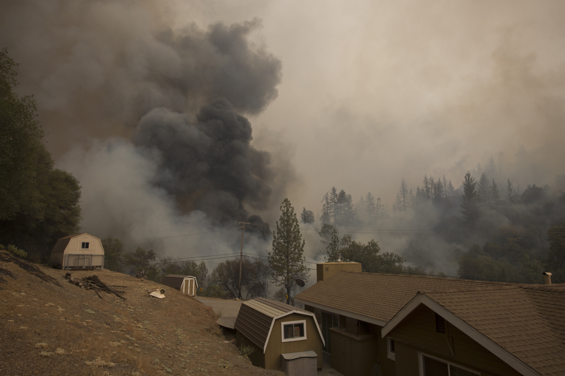 Smoke rises near a house on Mountain Ranch Road at the Butte Fire on September 13, 2015 near San Andreas, California.