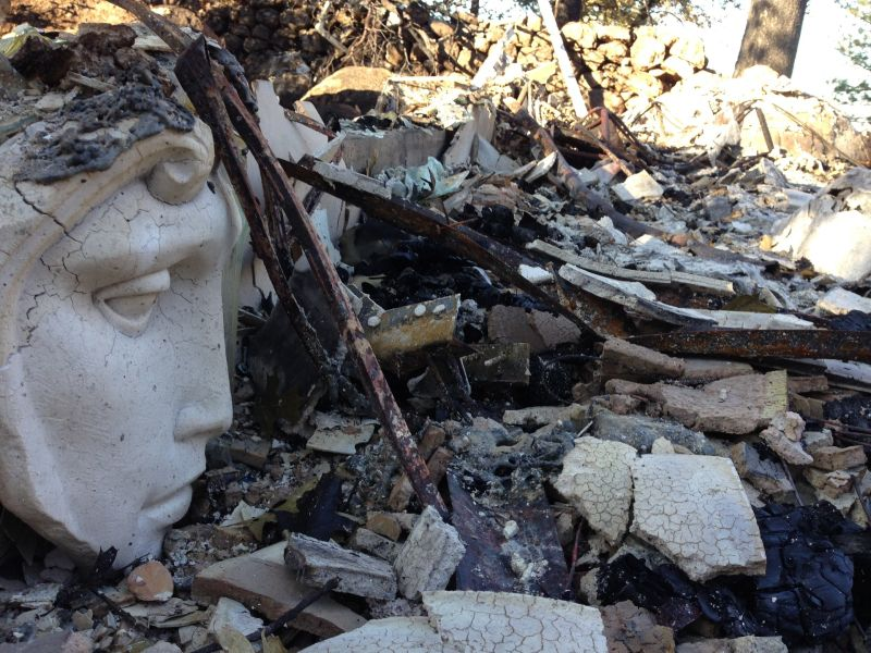 A statue looks out at the destruction. Ceramics and glass are some of the few things that can survive the high temperatures of a wildfire.