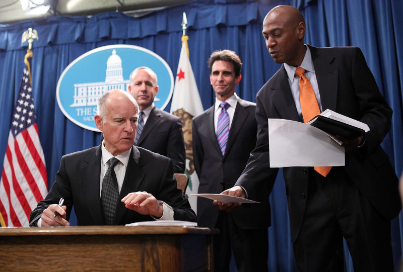 Gareth Elliott (R) hands Gov. Jerry Brown paperwork during a bill signing on March 24, 2011. A powerful lobbying firm announced Elliott would be joining their team just days after Elliott left the Brown administration.