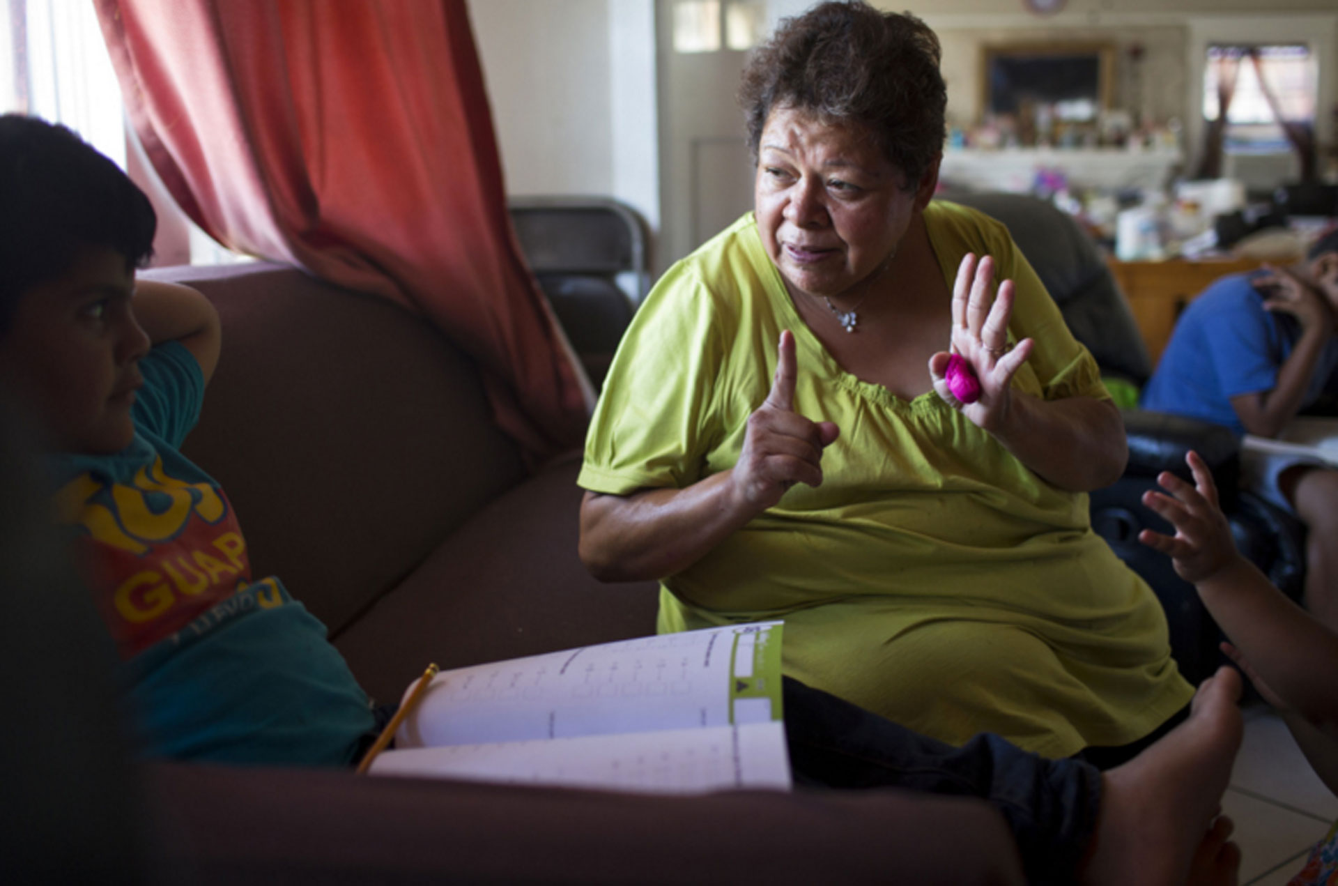 Maria Garcia, 58, works with her grandson, Pablo Andres Garcia, 6, on a math exercise in their South Los Angeles home.