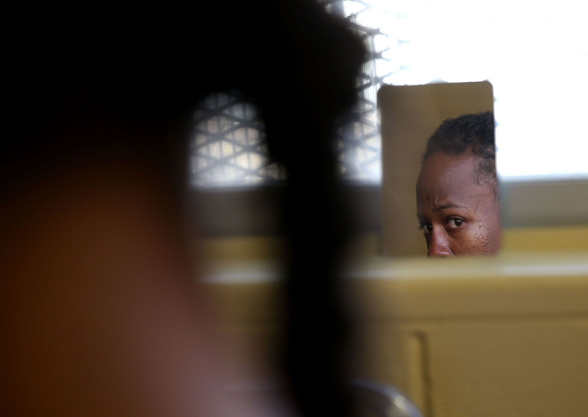 A San Quentin State Prison inmate looks in a mirror.