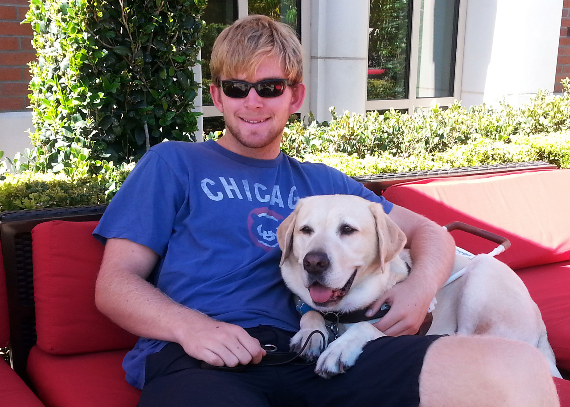 Jake Olson sits with his guide dog, Quebec. Inspired by his experiences with the USC Trojans as a 12-year-old, Olson tried out for his high school football team.