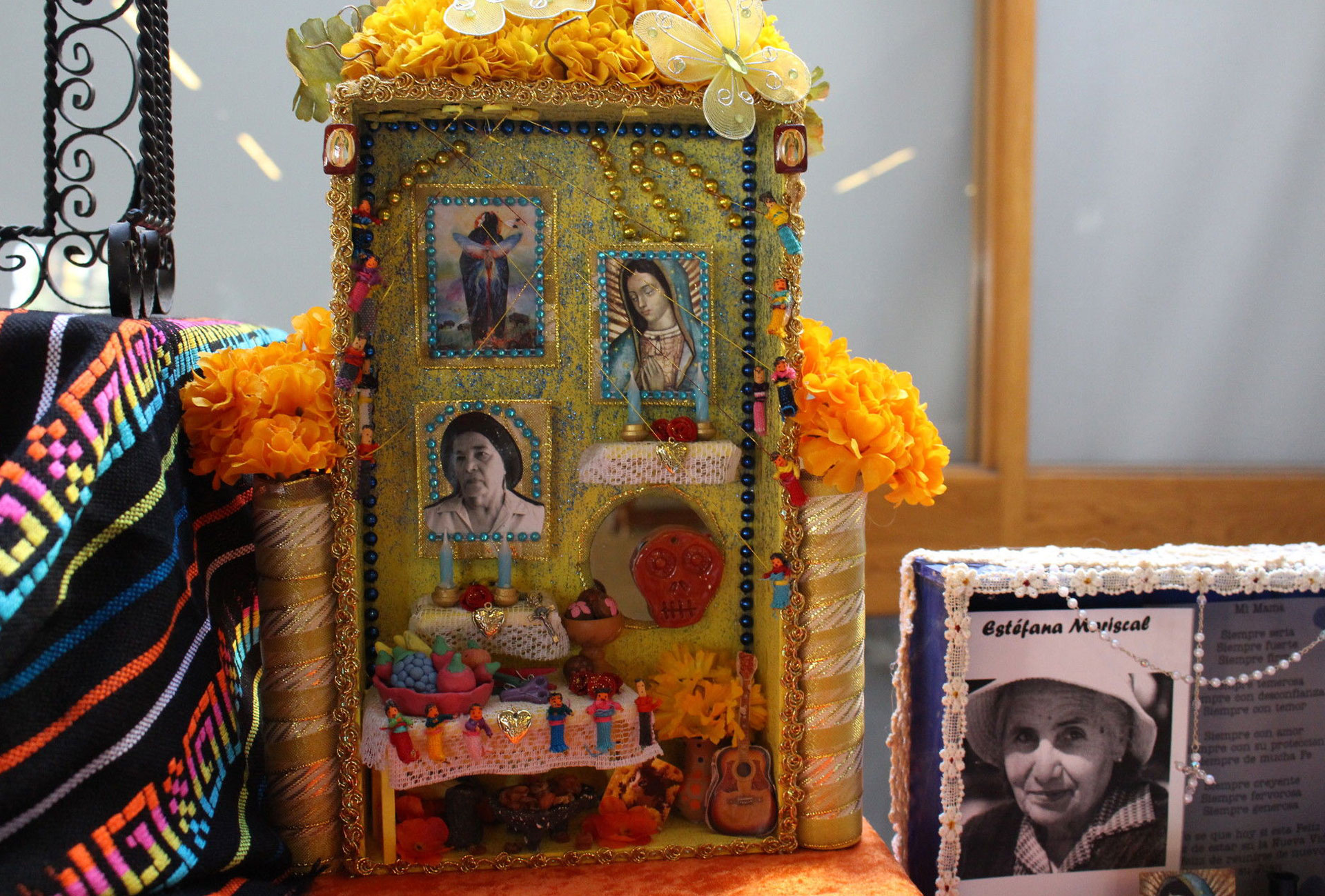 Nichos decorate an altar at the Oakland Museum of California for Day of the Dead. The central inch was made by art therapist Alicia Diaz to honor her grandmother. Diaz says was very religious and loved the color yellow.