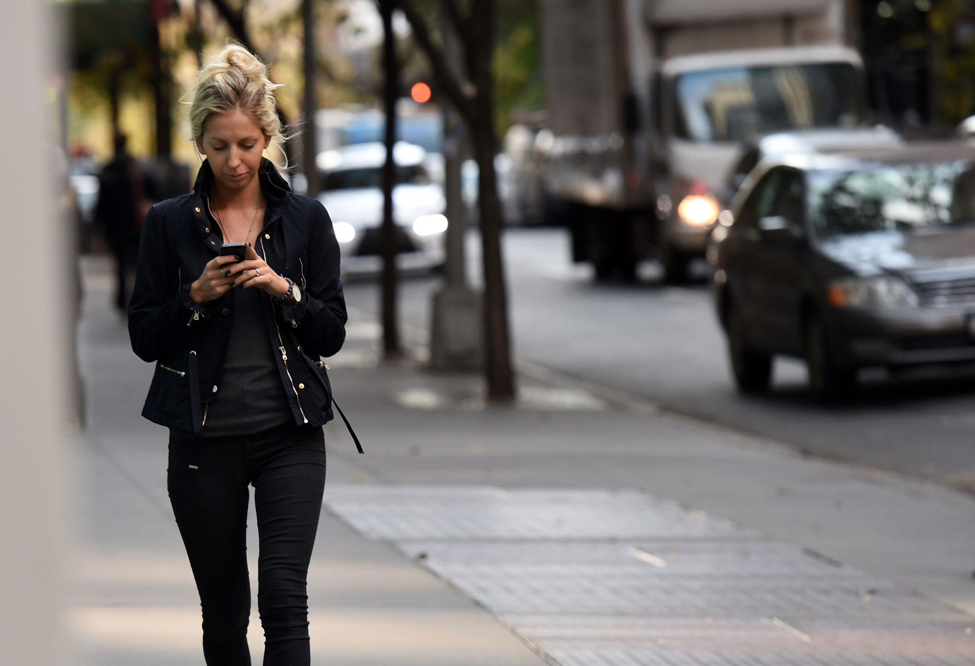 A pedestrian uses a smartphone