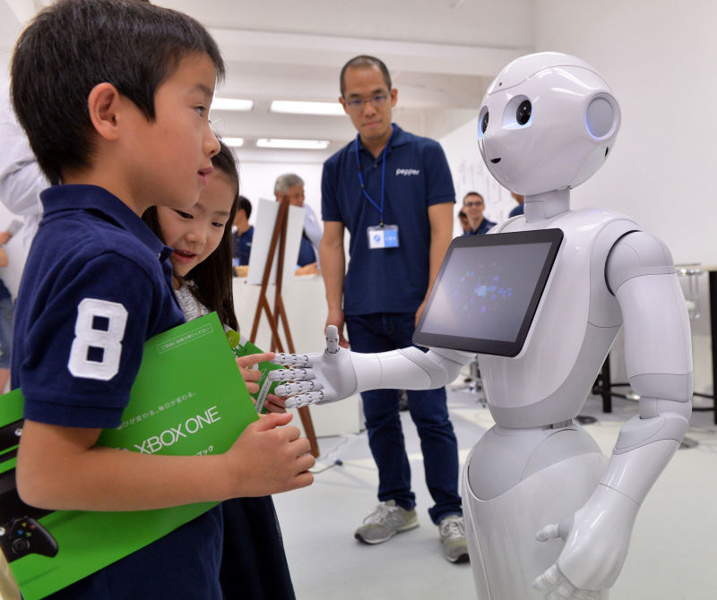 The humanoid robot Pepper chats with children at a high-tech gadgets exhibition in Tokyo.