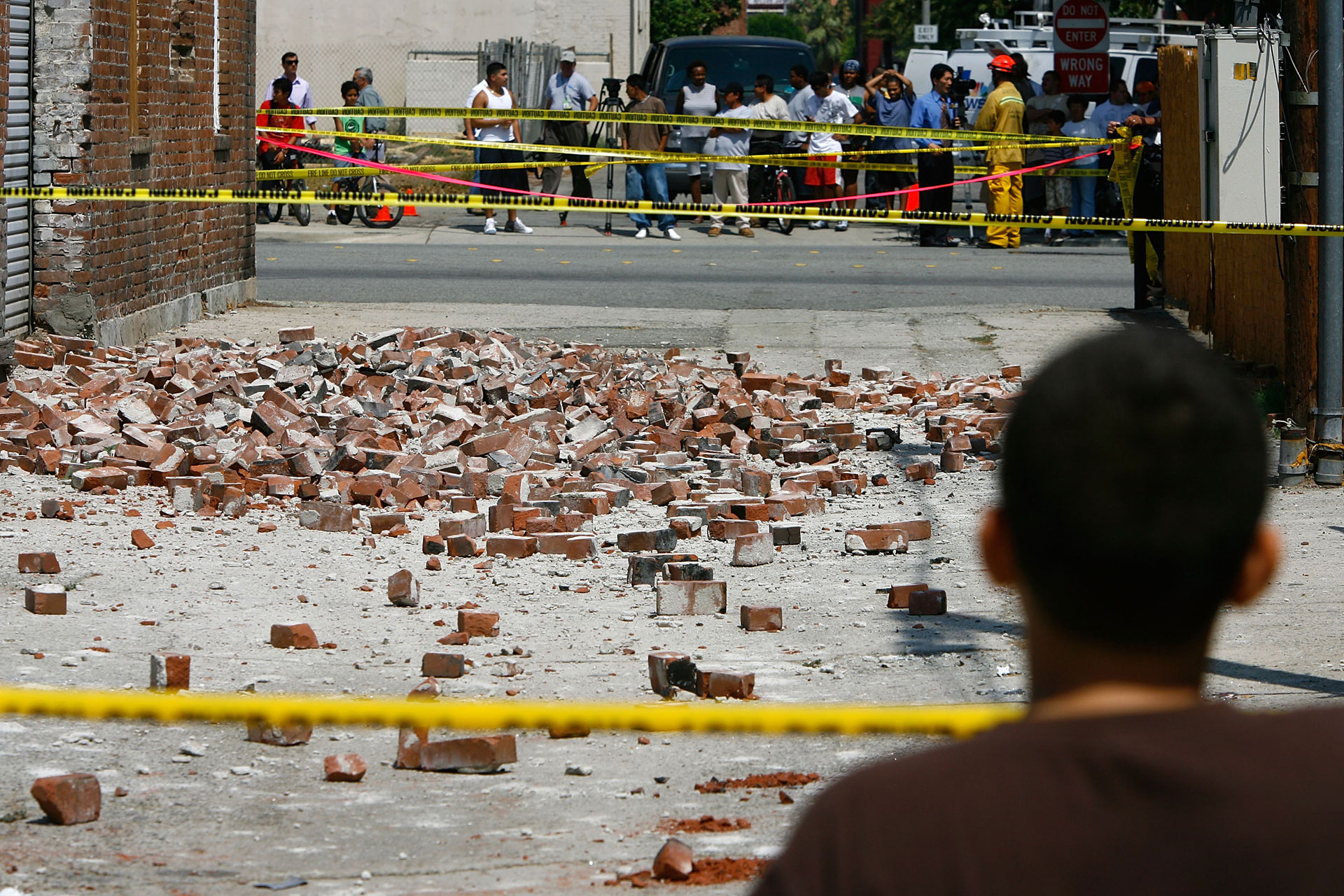 Spectators look at bricks which collapsed into an alley following a magnitude-5.4 earthquake on July 29, 2008 in Pomona.