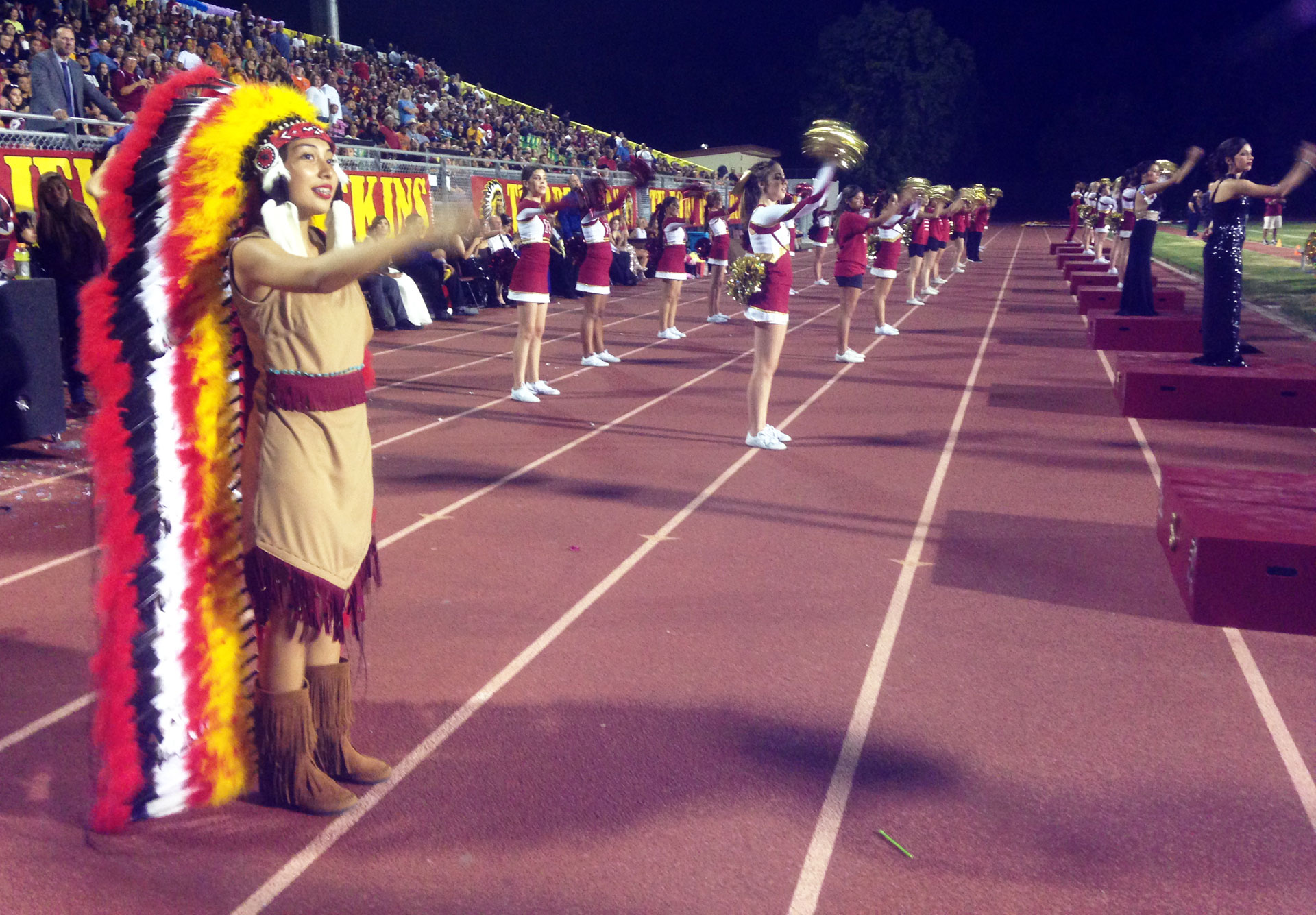 """The Redskins mascot roots for Tulare Union along with fans and cheerleaders, performing the """"tomahawk chop"""" gesture."""