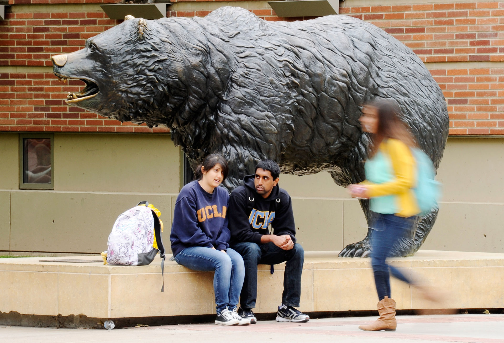 Students sit next to the Bruin Bear statue on the UCLA campus.