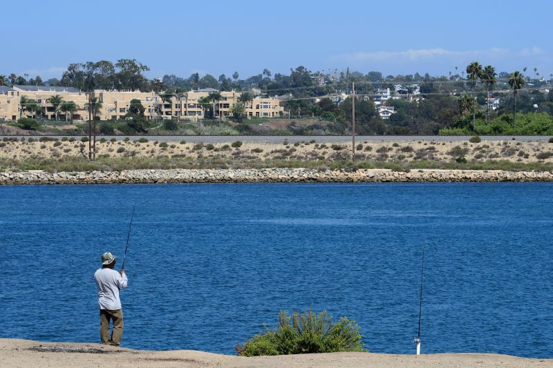 A fisherman casts his line into Agua Hedionda Lagoon, just across the shore from the Carlsbad desalination plant. The facility was designed and will be operated by Israel-based IDE Americas.
