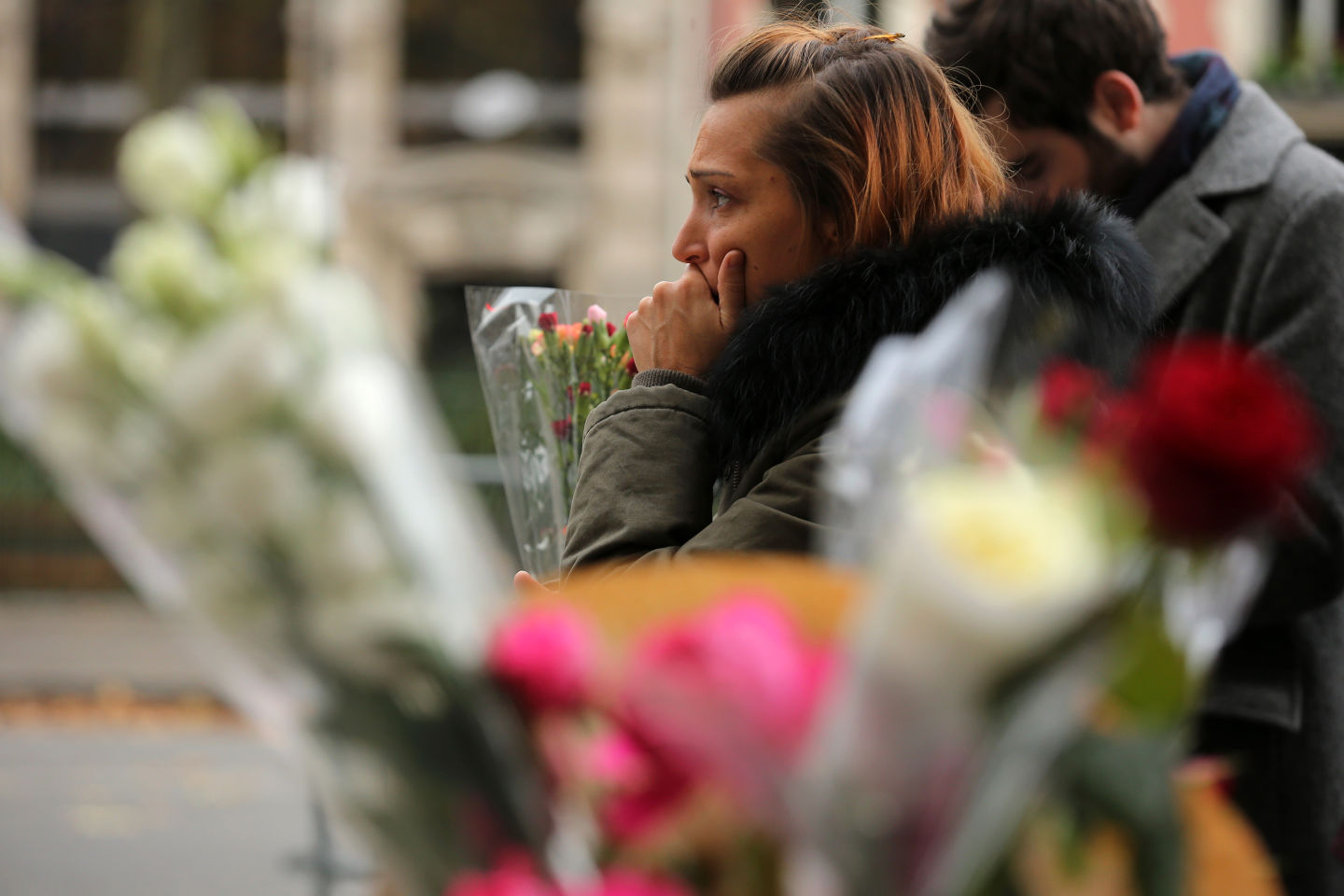 A woman reacts afetr placing flowers near the scene of yesterday's  Bataclan Theatre terrorist attack.  Christopher Furlong/Getty Images)