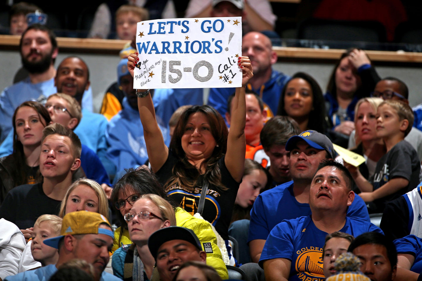 Fans celebrate the Golden State Warriors 15-0 season start with their 118-105 victory over the Denver Nuggets. (Doug Pensinger/Getty Images)