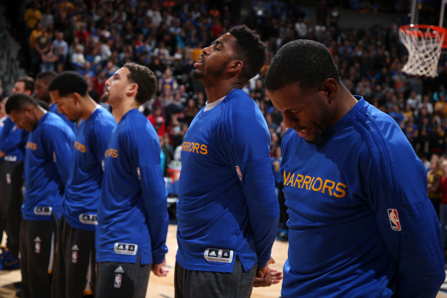 Andre Iguodala (R) and his teammates observe the national anthem prior to facing the Denver Nuggets Nov. 22, 2015. (Doug Pensinger/Getty Images)