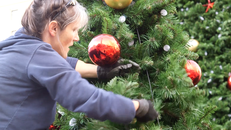 Lights and decorations are placed on the tree segments before they are stacked together.