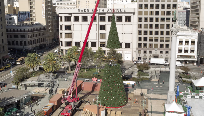 Workers use a crane to lift the final segment of the tree into place.