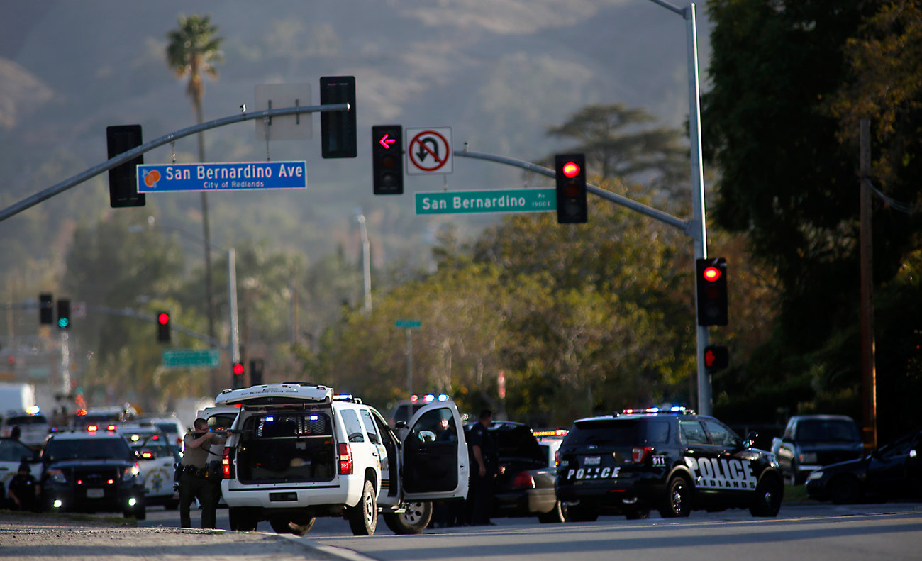 Police draw guns on San Bernardino Avenue while chasing suspects in an SUV. Later, police said alleged shooters Syed Farook, 28, and Tashfeen Malik, 27, were killed in a shootout with police