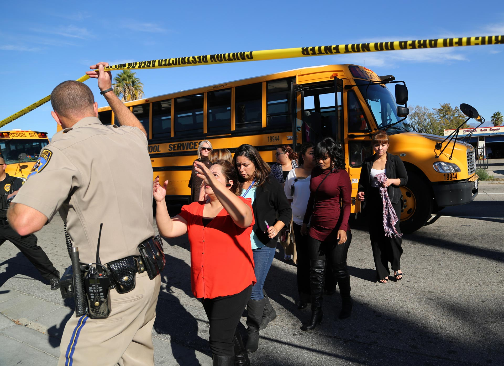 Employees and others are evacuated by bus from the site of a mass shooting at the Inland Regional Center in San Bernardino.