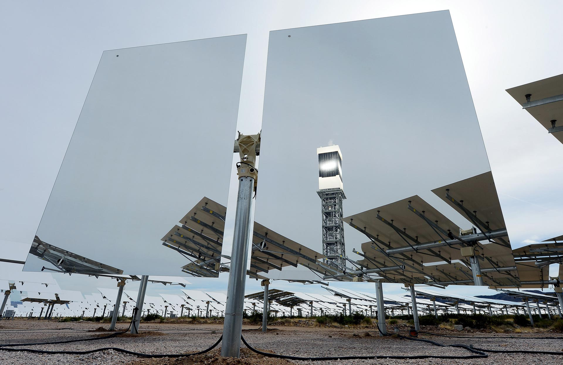 A solar receiver and boiler on top of a tower is reflected in a heliostat with two mirrors at the Ivanpah Solar Electric Generating System.