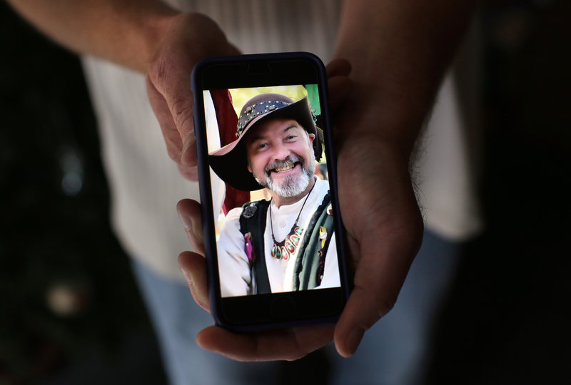 Ryan Reyes, 32, holds a photograph of his boyfriend of three years, Larry Daniel Kaufman, who was confirmed as one of the 14 people killed at the Inland Regional Center on Wednesday. The image was taken at a renaissance festival.