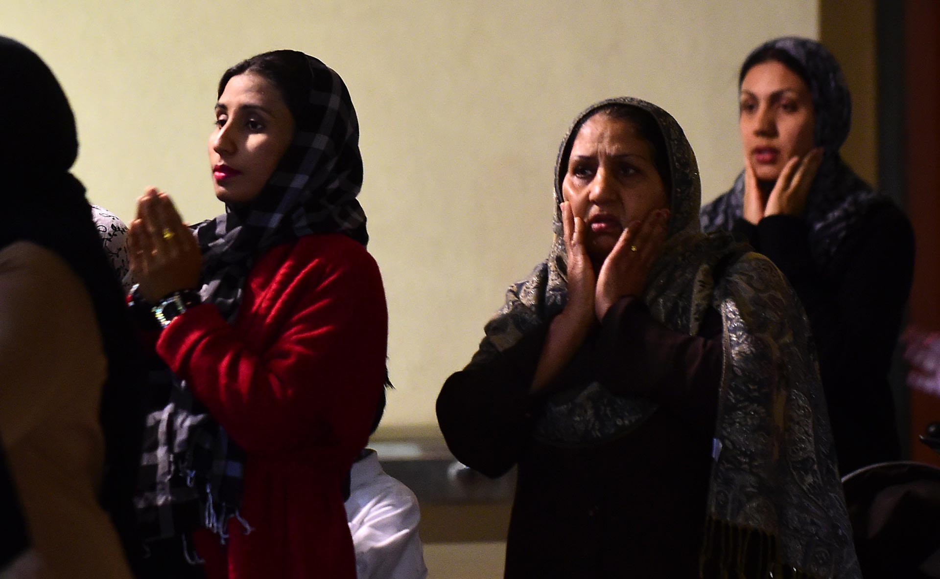 Muslim women gesture in prayer while congregating outside the Baitul Hameed Mosque in Chino on December 3, 2015. People attended a prayer vigil there to commemorate lives lost a day after the massacre in San Bernardino.