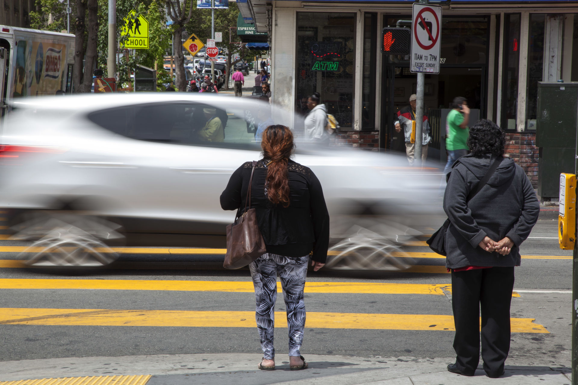Pedestrians wait to cross 24th Street in the Mission.