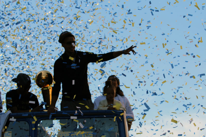 Stephen Curry rides through Oakland with the NBA Championship trophy during the Warriors Championship parade. (Adam Grossberg/KQED)