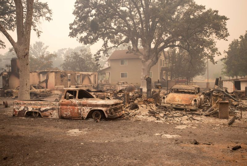 Burned out vehicles are surrounded by smoldering rubble as firefighters continued to battle the Valley fire in Middletown, California.