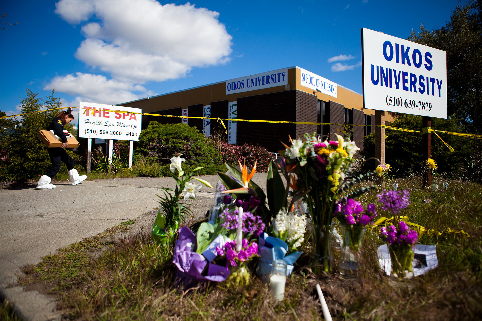 A member of the Oakland Police Crime Scene Investigation Unit walks past a makeshift memorial as she enters Oikos University where a gunman had gone on a shooting rampage.