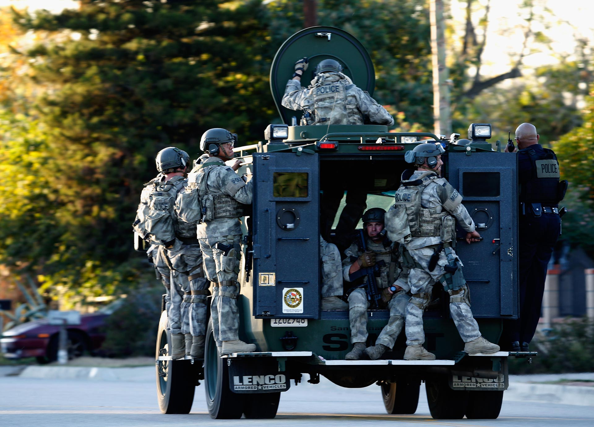 SWAT officers enter a neighborhood where suspects were believed to be after the mass shooting at San Bernardino's Inland Regional Center on Dec. 2, 2015.