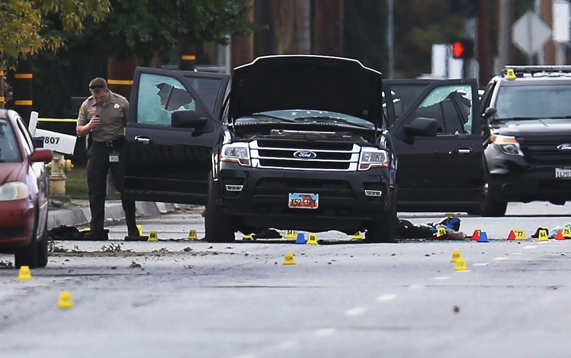 Law enforcement officials investigate around the SUV vehicle where suspects of the shooting at the Inland Regional Center were killed on December 3, 2015 in San Bernardino.