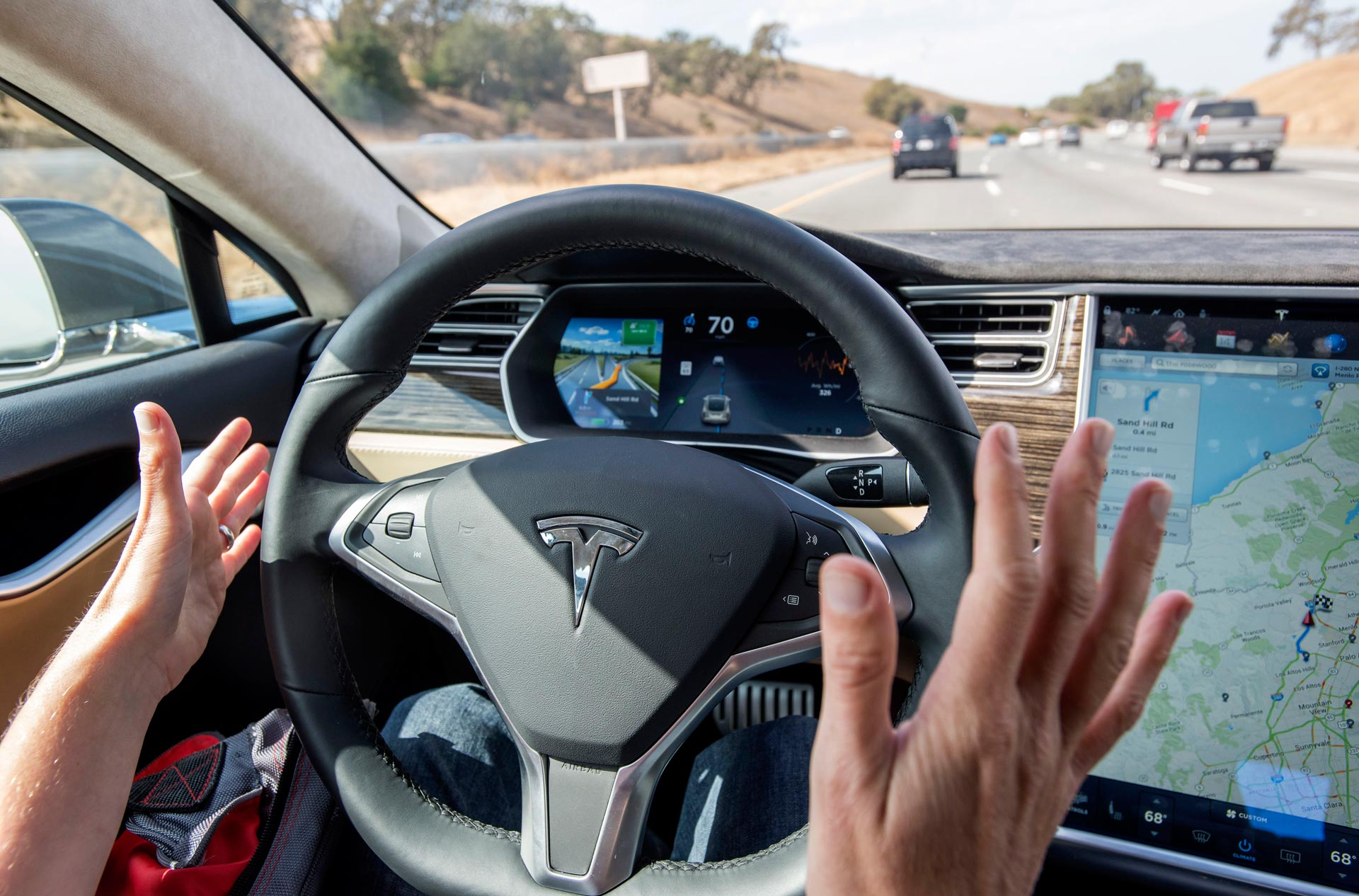 A member of the media test drives a Tesla Model S car equipped with Autopilot. Tesla is the largest seller of electric vehicles in the nation.