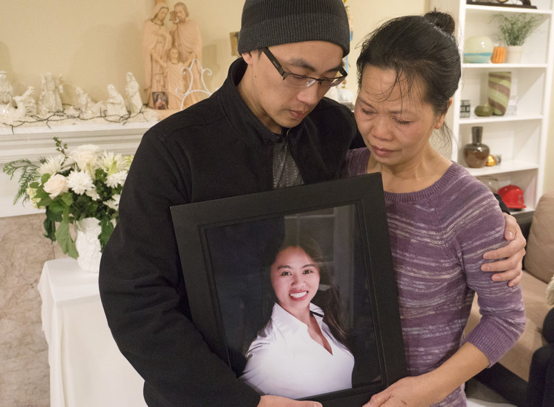 At their home in Santa Ana, Calif., Trung Do (L) and Vanessa Nguyen and hold a photograph of their sister and daughter Tin Nguyen, who died in the mass shooting.