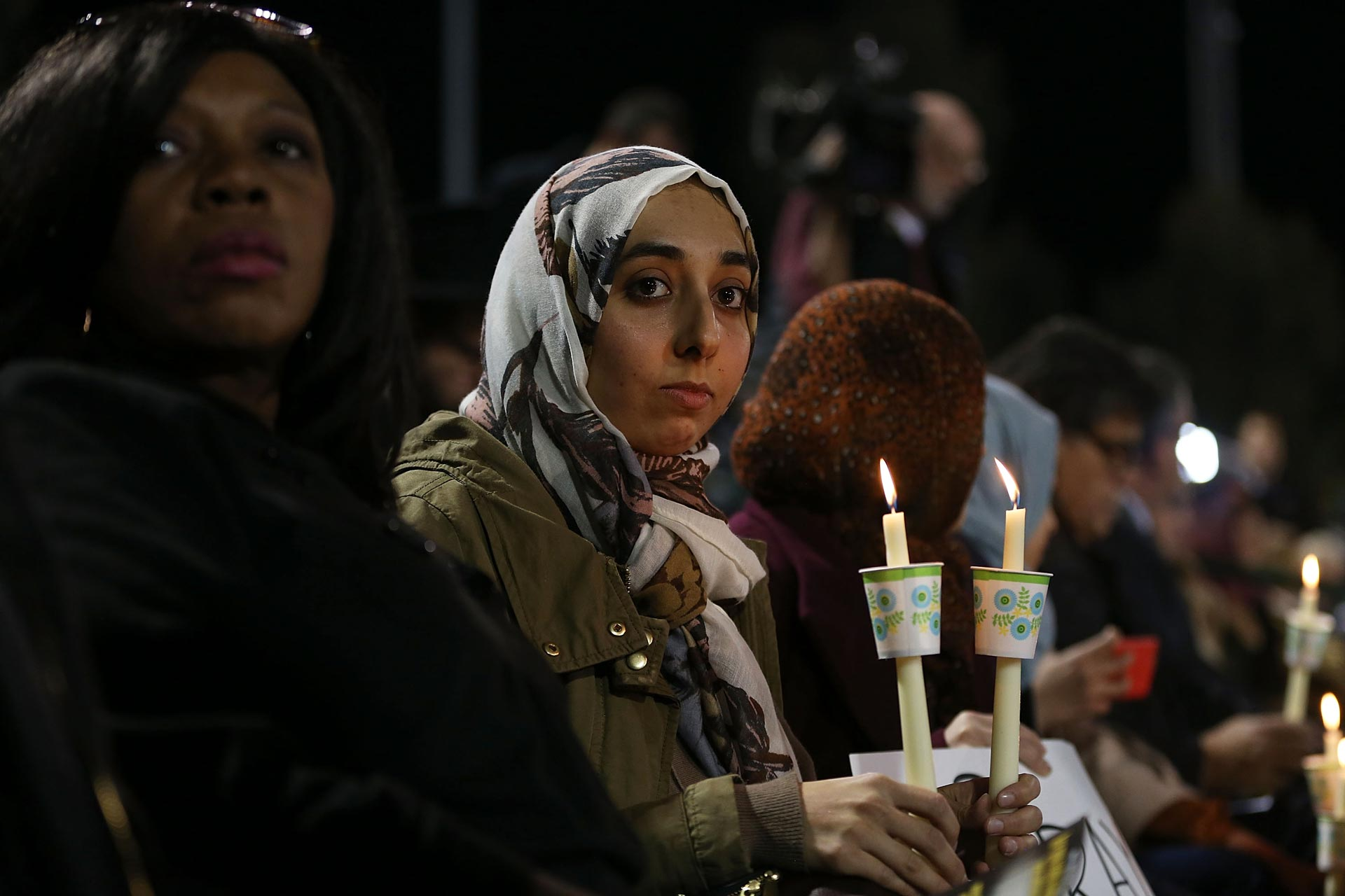 People hold candles as they attend a vigil at the San Manuel Stadium to remember those injured and killed during the shooting at the Inland Regional Center on Dec. 3, 2015 in San Bernardino.