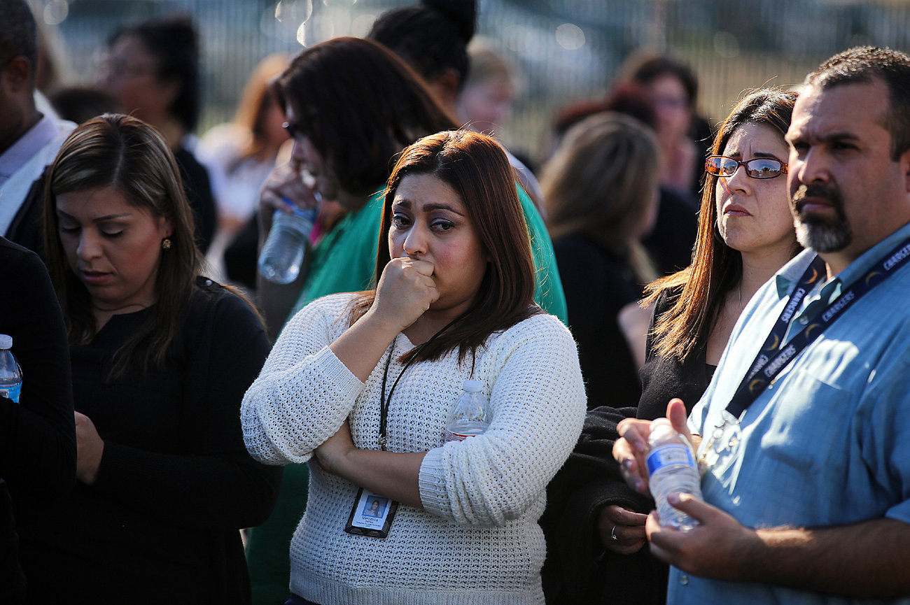 Workers wait to be evacuated by bus as police search for suspects on Wednesday, Dec. 2 in San Bernardino.