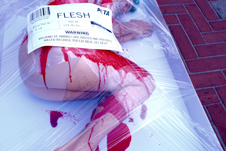A student protested wrapped and labeled as meat. The label reads: 'Warning: Billions of animals are abused and violently killed because you eat meat. Get help!'