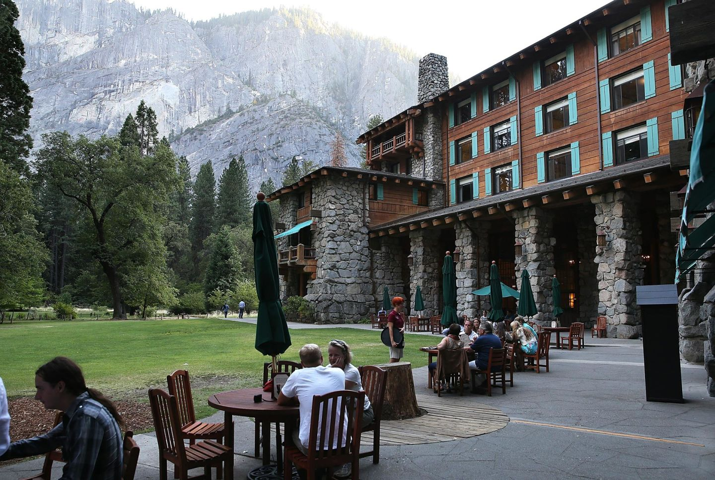 Park visitors sit outside the historic Ahwahnee Hotel, now to be called the Majestic Yosemite Hotel.
