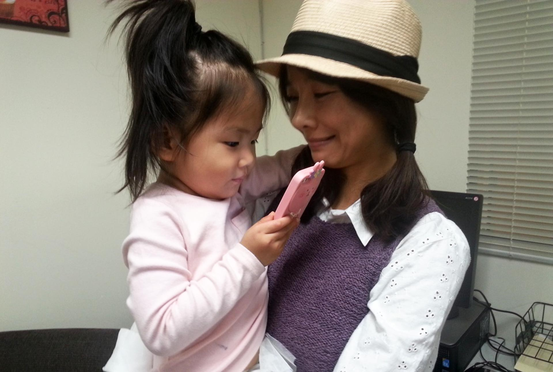 Ahyun and her three-year-old daughter, Joanna, watch anime while visiting the offices of Korean American Family Services. Ahyun, 31, is a survivor of domestic violence and receives counseling at the agency.