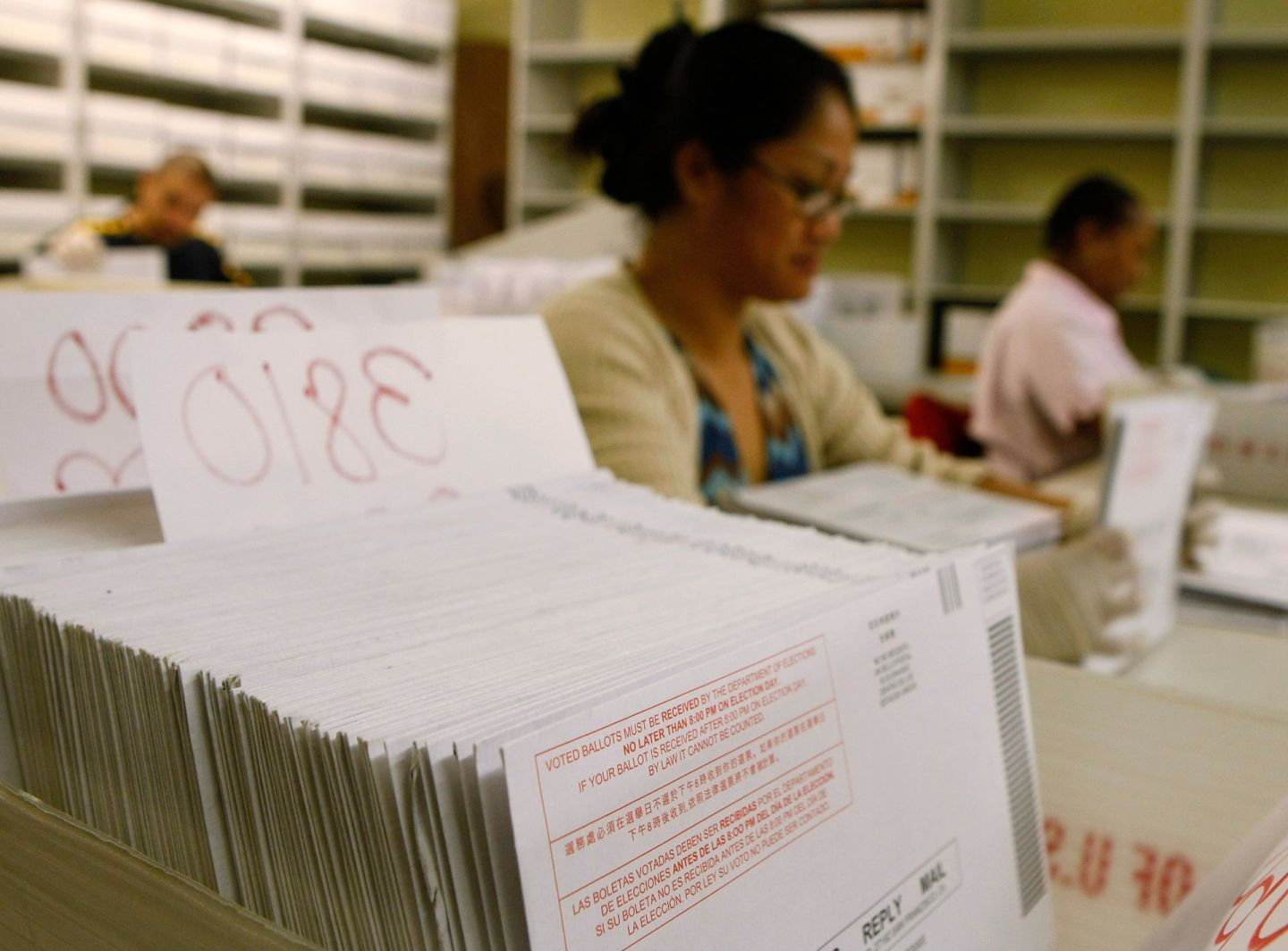 Workers at the San Francisco Department of Elections sort stacks of vote-by-mail ballots.