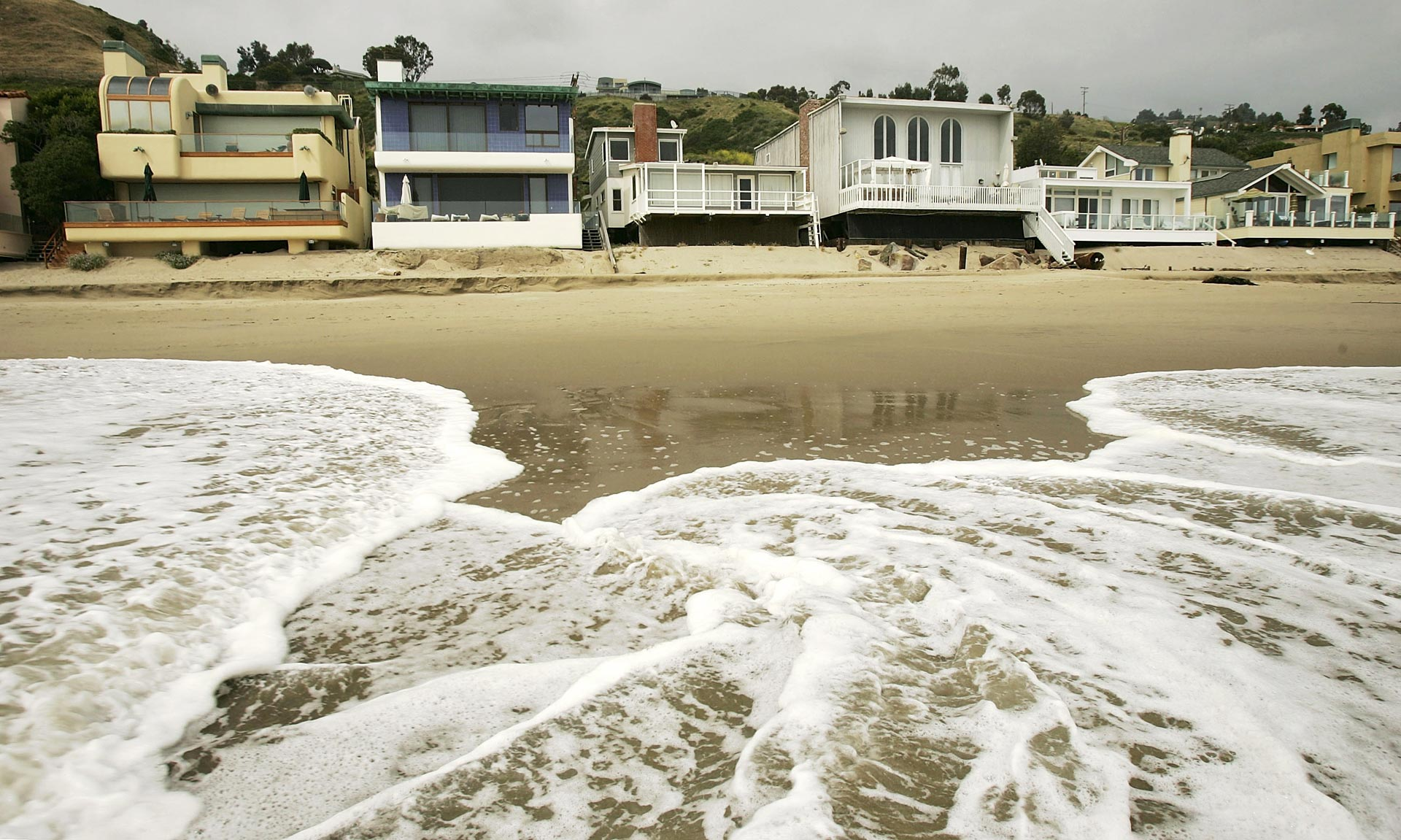 Luxurious beach houses crowd the shoreline hiding Carbon Beach in Malibu. A lengthy legal battle over public access to the beach culminated in 2005, with music producer David Geffen allowing a public pathway across his property in exchange for permits from the Coastal Commission to begin building a Cape Cod-style compound across multiple lots.