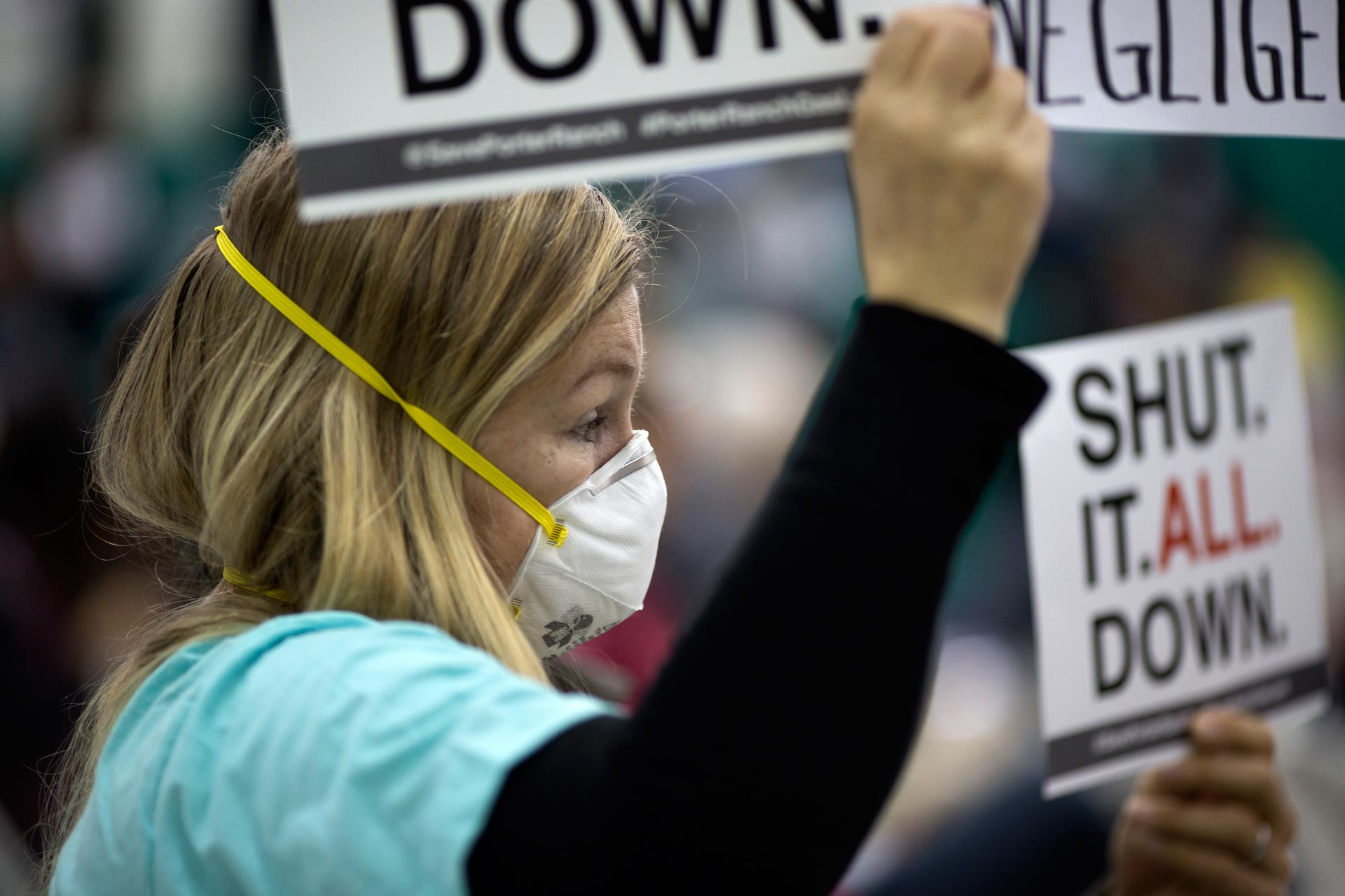 A woman holds a sign at a public hearing before the South Coast Air Quality Management District (AQMD) regarding a proposed stipulated abatement order to stop the massive natural gas leak, on January 16, 2016 in Granada Hills, near Porter Ranch.