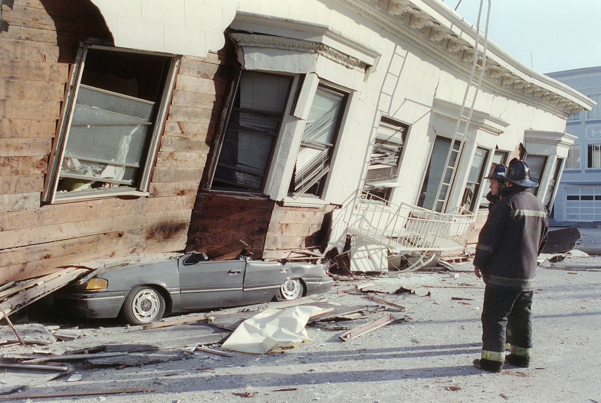 Firemen stand in front of a collapsed house in the Marina district after the 1989 Loma Prieta earthquake in San Francisco.