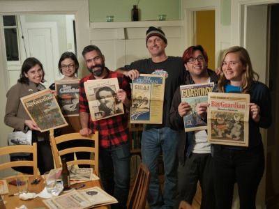 Former Bay Guardian staffers hold up old editions of the paper on Oct. 15.