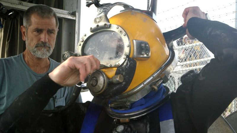 Diver Kevin Nekimken puts on his helmet before a recent dive at the Port of Oakland. (Alan Toth/KQED)