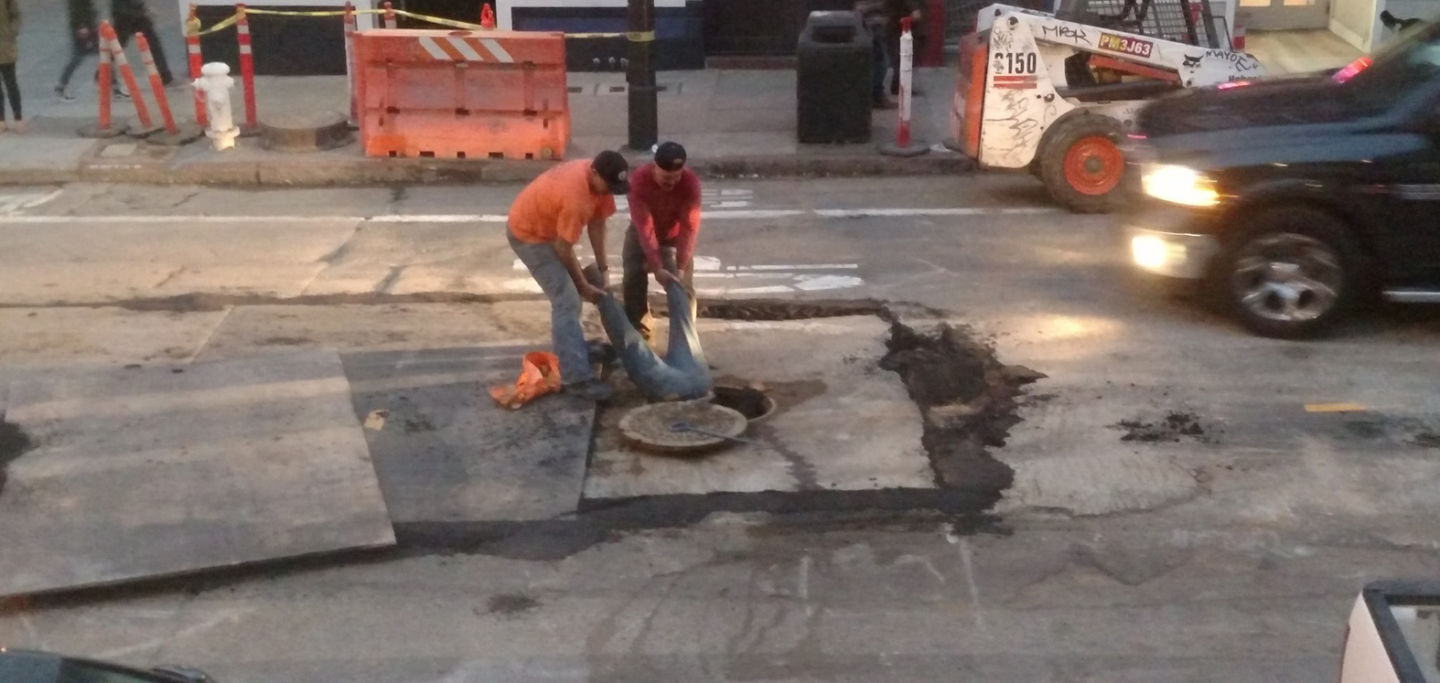 Two workers from Synergy Project Management hold a foreman by his ankles as he works in a Haight Street manhole on July 21, 2015.  San Francisco Public Works