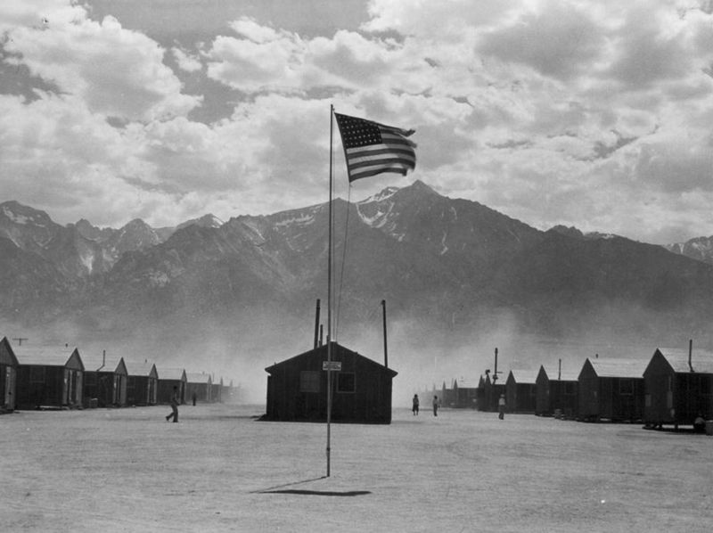 Scene of barrack homes at this War Relocation Authority Center for evacuees of Japanese ancestry. A hot windstorm brings dust from the surrounding desert.