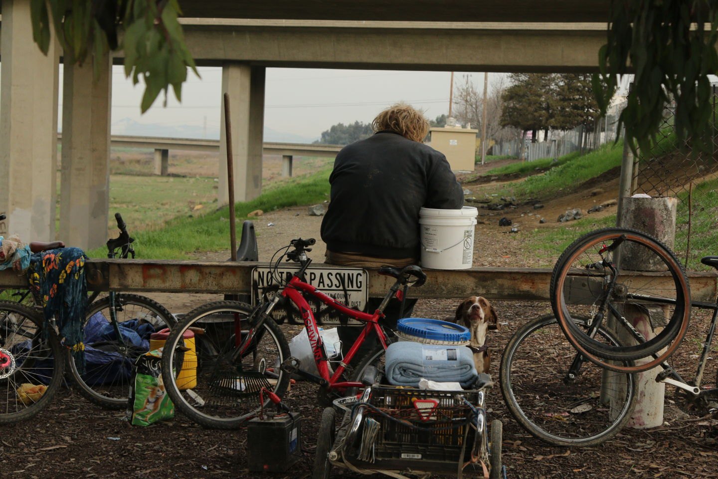 A homeless man sits at his encampment in Contra Costa County, where volunteers warned of a rainstorm that could flood the canal under the overpass where he was situated.  Ericka Cruz Guevarra/KQED