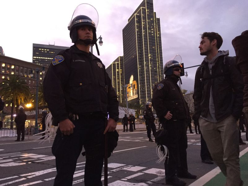 San Francisco Police officers keep a crowd protesting how San Francisco handles its homeless population corralled on a sidewalk across the street from NFL 'fan village' Super Bowl City.