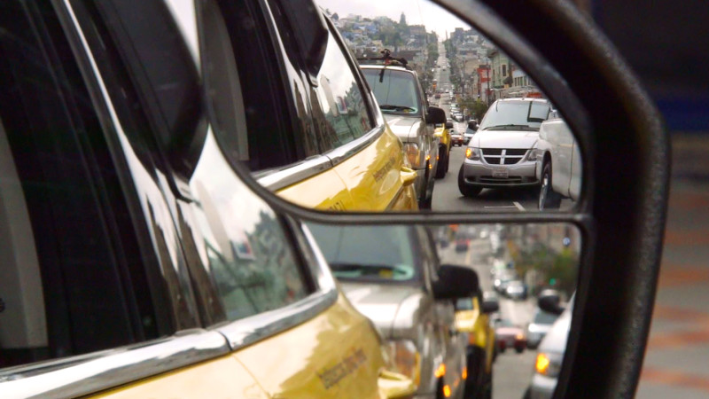 Looking back through one of the sideview mirrors on John Han's taxicab. (Adam Grossberg/KQED)