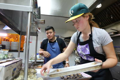 Chef Tee and Filipino Kitchen Project Manager Caitlin Preminger prepare meals for 30 guests.