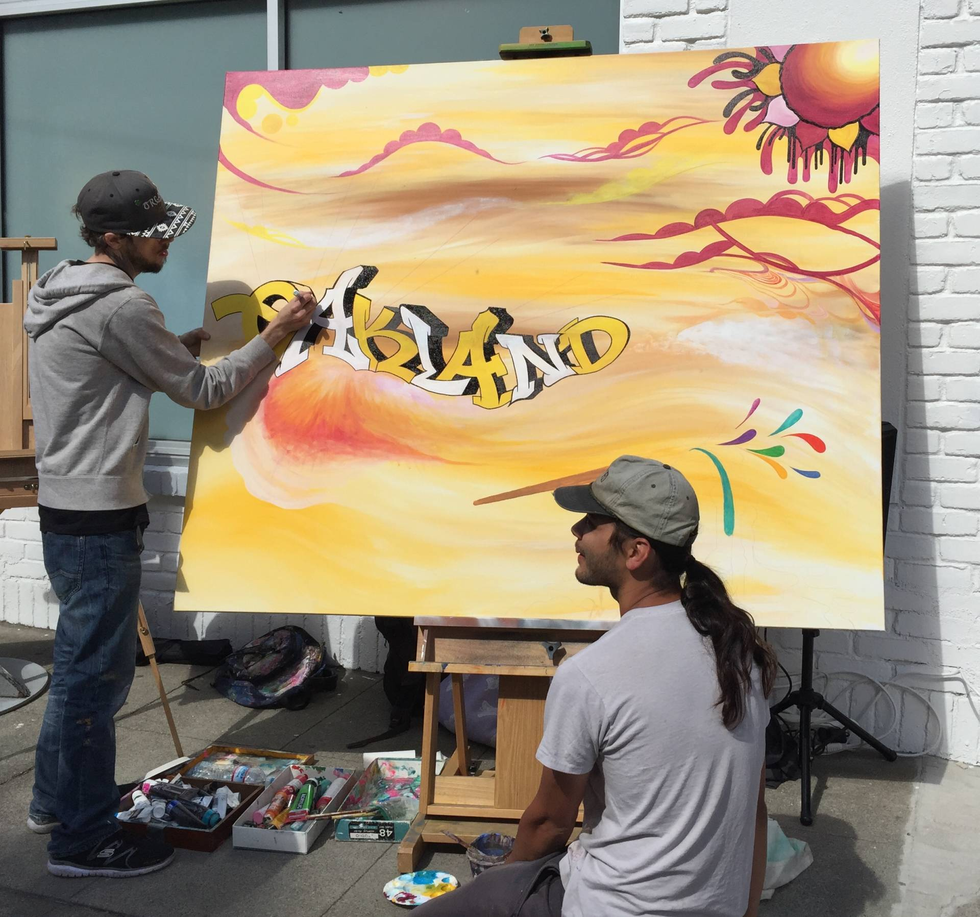 Artists Dustin Derego and Jared Roses work on a canvas for the grand opening of FLAX art & design in Oakland on March 31, 2016.