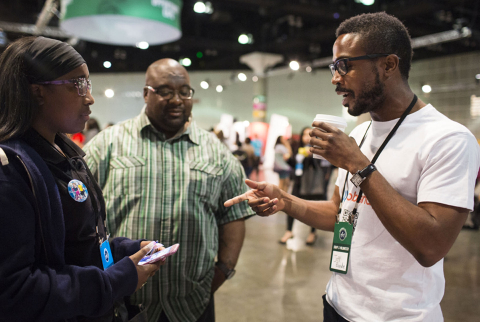 Jeff Boodie (R), founder and CEO of JobSnap, explains his app to 16-year-old Kamiya Williams during the Los Angeles Opportunity Hiring Fair at the L.A. Convention Center on Feb. 11, 2016.